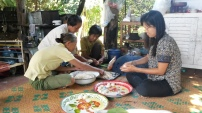 """Preparing Lanna """"bread"""" - rice cakes with sweet coconut stuffed inside, wrapped in a banana leaf, and steamed."""