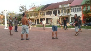 Playing local game, like hacky sack, in Cambodia.